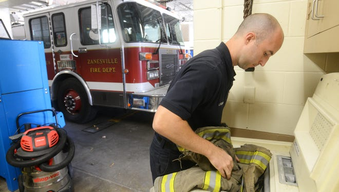 Zanesville Fire Department Firefighter Levi Vought loads a turnout jacket into a special washing machine built for washing fire gear at the department's Central station in Downtown Zanesville.
