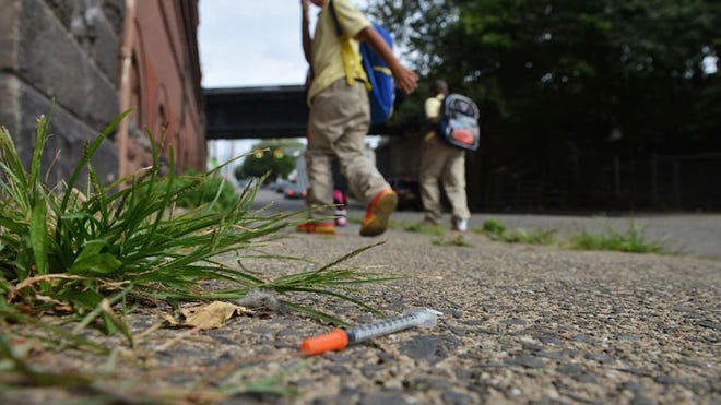 School age children walk past a needle on the sidewalk of Governor St. on the way home from school.