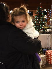Emma Swindelo, 2, awaits Santa in the arms of her mom,