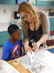 Katharyn Jones helps Brenton Rucker thread a string