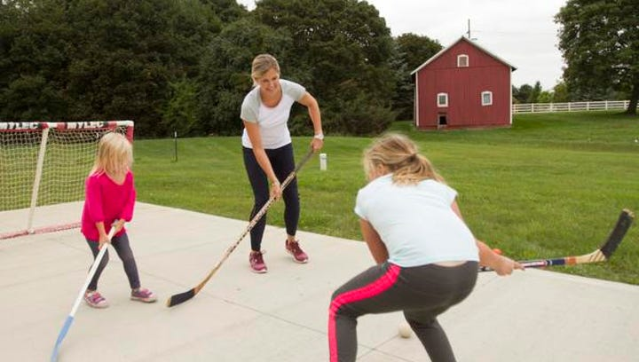 Former Hamburg Township resident Courtney Alexander plays street hockey with her children Lexi, 3, at left, Brooke, 8, and Chase, 6 (not shown) in the driveway of their Saline-area home. Alexander, who was revived with an automatic external defibrillator after suffering from a sudden coronary artery dissection in February 2013, is starting a fundraising drive to buy AEDs for all Livingston County police agency vehicles.