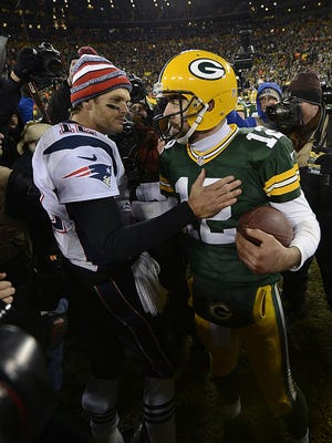 Green Bay Packers quarterback Aaron Rodgers and New England Patriots quarterback Tom Brady exchange words after Sunday's game at Lambeau Field. The Packers defeated the Patriots 26-21.