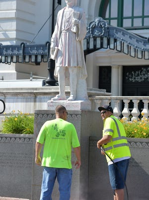 Workers clean the Christopher Columbus statue in front of Worcester's Union Station after it was vandalized last month.
