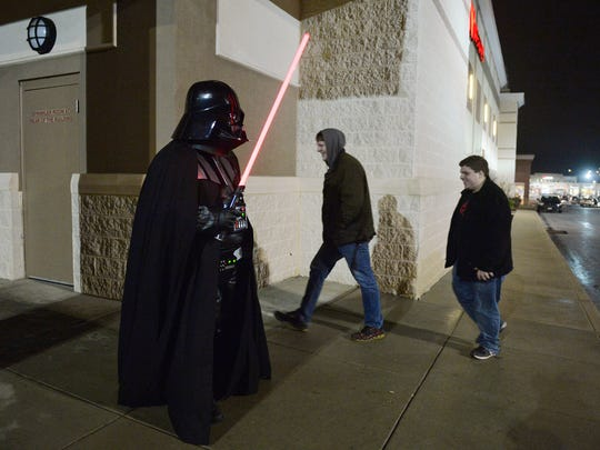 "Doug Dzubinski of Windsor, dressed as Darth Vader, greets fellow fans outside before having to leave his helmet and lightsaber in his car at the premiere of ""Star Wars: The Force Awakens"" on Thursday, Dec. 17, 2015, at Frank Theatres in York Township. The movie is the first ""Star Wars"" film since the Walt Disney Company acquired Lucasfilm in Oct. 2012. Like many other theatres nationwide, Frank Theatres prohibited masks and toy weapons, but the Force was strong with many fans who arrived costumed or wearing themed clothing."
