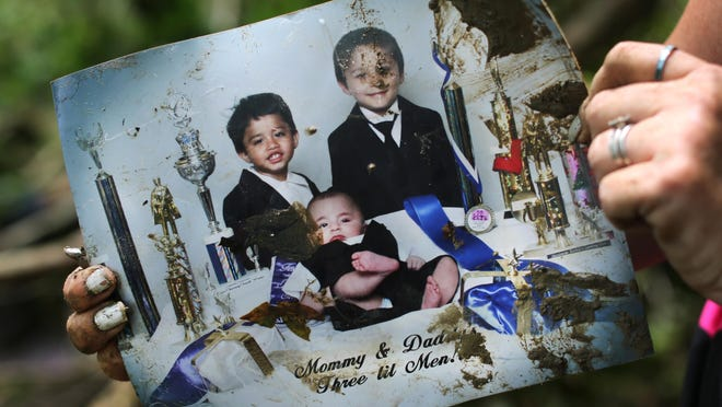 An old family photo is rescued from the bank of the Red Oak Creek in Ripley. A late evening flash flood swept a mobile home off its foundation, killing a mother, six months pregnant, and her two young children. Her fiance and two older boys survived. The two older children in this photo survived.
