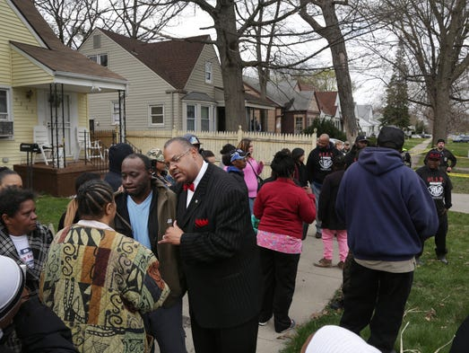 People gather by the home where Terrance Kellom, 19