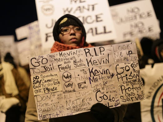 A protestor holds a sign while marching with civil