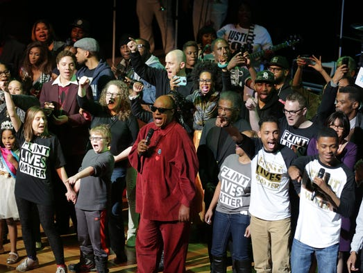 Stevie Wonder is joined onstage by performers and supporters