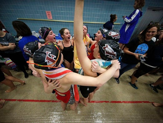 Menomonee Falls swimmers huddle and cheer before the