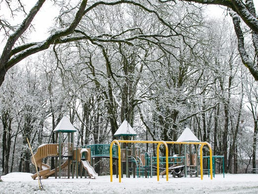 A light dust of snow sticks to playground equipment