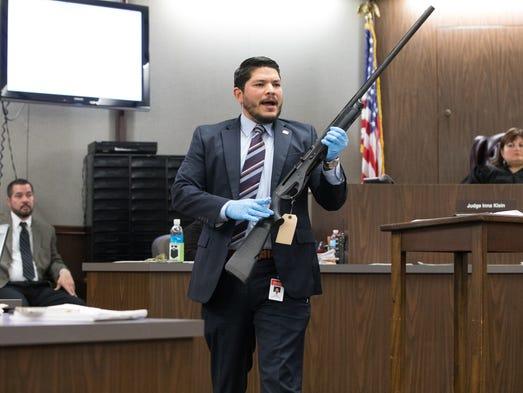 District Attorney Mark Gonzalez holds a shotgun used