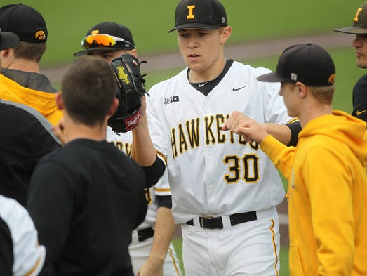 Iowa pitcher Nick Gallagher high-five's teammates between