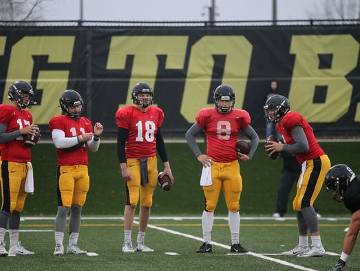 Iowa's quarterbacks line up for drills during practice