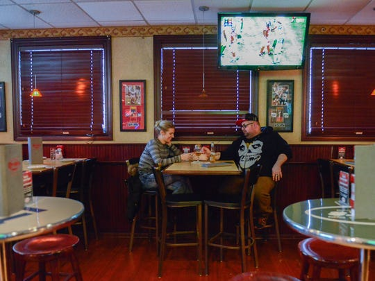 Laurie Holinka and Joseph Liloia, both of Rutherford, watch football at Redd's Restaurant on Sunday.