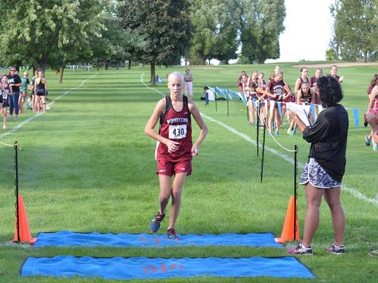 Winneconne junior Abby Johnson crosses the finish line at the Winneconne Invitational earlier this season.