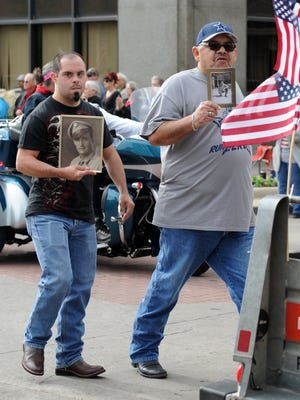 Mike Griego (right) and his stepson Joseph Adcox carry the photos of Griego's father, Manual Griego, and stepfather, Tom Elliott, who served in the Army during WWII at the Veterans Day Parade Saturday, Nov. 5, 2016, in Downtown Wichita Falls.