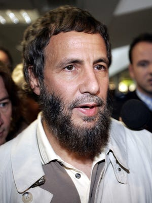 "Yusaf Islam, center, formerly known as the rock star Cat Stevens arrives at London's Heathrow airport after being refused entry to America Thursday, Sept. 23, 2004. U.S. officials, who had ordered Islam taken off a London-to-Washington flight on Tuesday, said he was on a security watch list because of suspicions that he was associated with potential terrorists. ""I'm totally shocked,"" Islam told a swarm of reporters as he came through the arrivals area at Heathrow airport. (AP Photo/Adam Butler)"