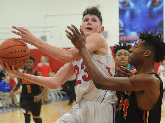 Cooper's Deven Bailey (23) drives to the basket while Lubbock Coronado's Bronzea Giddens defends. The Mustangs beat Cooper 77-56 in the District 4-5A game Friday, Jan. 19, 2018 at Cougar Gym.