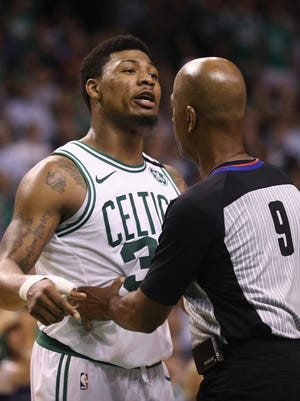 Marcus Smart is held back after getting into an altercation with JR Smith.