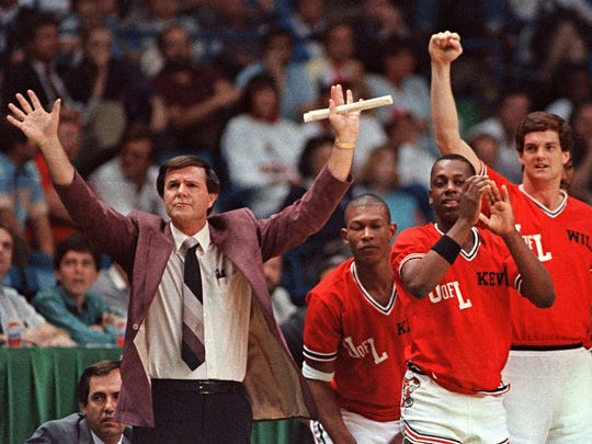 Louisville coach Denny Crum gestures toward his team as players from the bench begin to celebrate during the closing moments of their 88-77 victory over LSU in the NCAA semi-finals in 1986. Six years earlier Crum clenched the team a championship in Indianapolis.