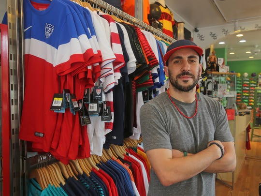 Danny D'Angelo, owner of Village Soccer Shop in Tarrytown, stands near a row of soccer jerseys representing teams from different countries June 10, 2014. Owner Daniel D'Angelo says that business has been brisk in anticipation of the World Cup tournament, which begins on Thursday.