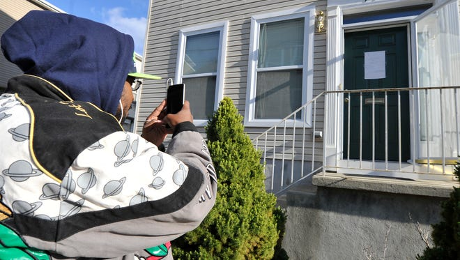 Tyron Miller takes a photo of the Harrisburg home of 19-year-old terrorism suspect Jalil Ibn Ameer Aziz on Friday. Aziz is accused of using the internet to spread propaganda of the ISIS terrorist group, advocate violence within the U.S. and aid terrorists in traveling to the Islamic State.
