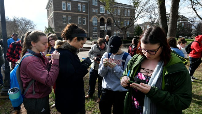 """Maryville College student Allison Potts, left, uses Brianne Sidner's back as they write messages about """"how they will create peace with themselves and their community"""" during  the National School Walkout Wednesday, Mar. 14, 2018 in Maryville, Tenn. At right is Lili Rafalski."""