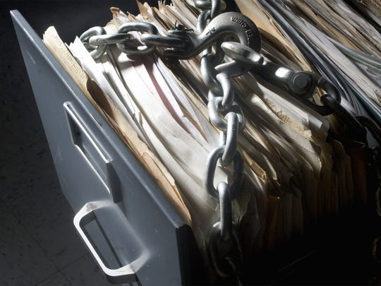 Photo-illustration of a file cabinet that is chained