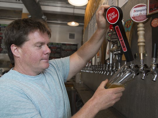 Owner Russ Robinson pours Pliny the Elder, a beer that