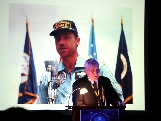 Apollo 15 Command Module Pilot Al Woden speaks in front of a slide depicting himself as a young man, when Apollo 15 landed on the moon in 1971. Worden was the keynote speaker for the 2015 NMMSH International Space Hall of Fame induction ceremony Oct. 3.