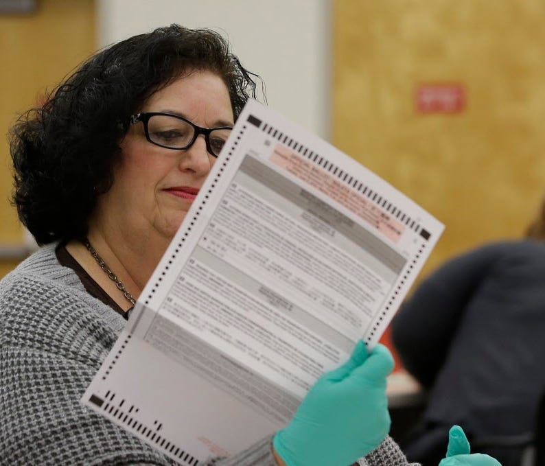 Beverly Darm, an election clerk at the Sacramento County Registrar of Voters, inspects a mail-in ballot May 30, 2018, in Sacramento.