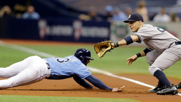 Tampa Bay Rays' Brad Miller (13) dives back to first