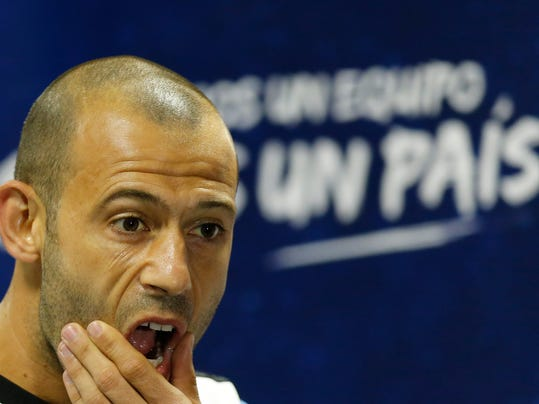"""Argentina's Javier Mascherano gestures at the start of a news conference in Vespesiano, near Belo Horizonte, Brazil, Sunday, July 6, 2014. The sign reads in Spanish """"one country."""" Argentina will face Netherlands on their semifinal match of the 2014 World Cup soccer tournament on July 9 in Sao Paulo.(AP Photo/Victor R. Caivano)"""
