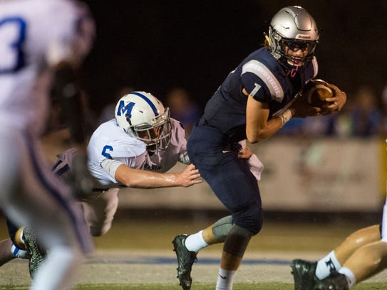 Reitz quarterback Eli Wiethop (1) gets tackled by Memorial's