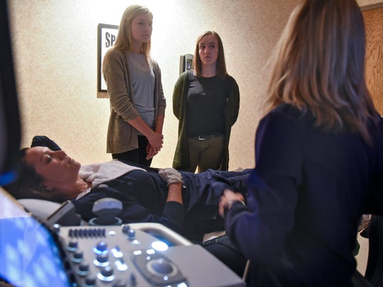 Students Missy Prom and Rachel Merchlewicz listen as Naomi Baker and Maryann Burrows talk about the skills required to be an medical sonographer Friday, March 23, in the ultrasound department at St. Cloud Hospital.