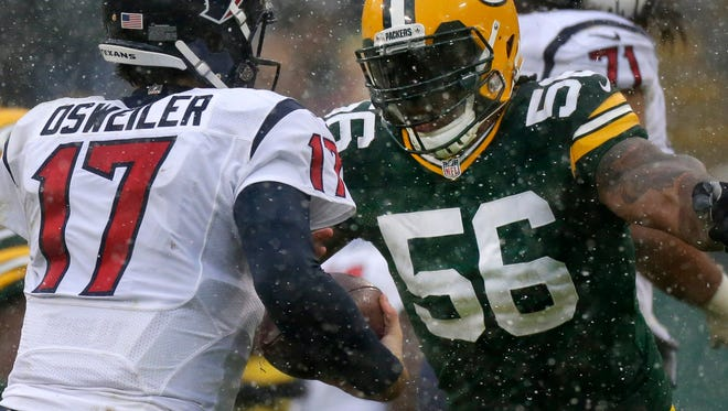 Green Bay Packers outside linebacker Julius Peppers (56) sacks Houston Texans quarterback Brock Osweiler (17) during the second quarter of their game Sunday, December 4, 2016 at Lambeau Field in Green Bay, Wis.