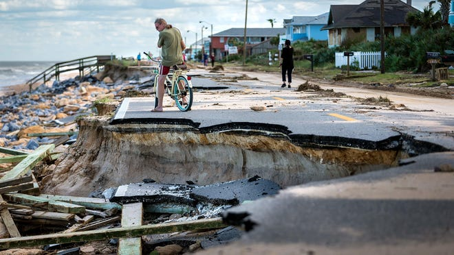 """Kevin O'Connor, of Long Beach, New York, surveys a section of State Road A1A damaged by erosion after Hurricane Matthew passed the east coast of Florida in October 2016. O'Connor said he owns two homes in Flagler Beach and came down to try to protect his investments. """"If this were a direct hit, we wouldn't be standing here. Twenty or 30 years ago when I first started coming here, the beach was way deep, but now, the last 10 years after those other storms, there is nothing left,"""" O'Connor said."""