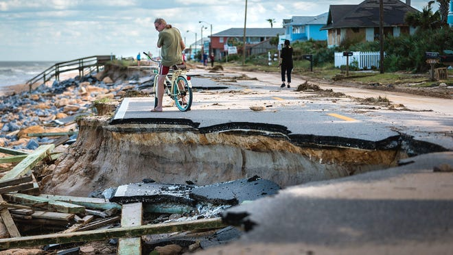 Kevin O'Connor, of Long Beach, N.Y., surveys a section of State Road A1A damaged after Hurricane Matthew passed the east coast of Florida in October. O'Connor said he owns two homes in Flagler Beach and came down to try to protect his investments.
