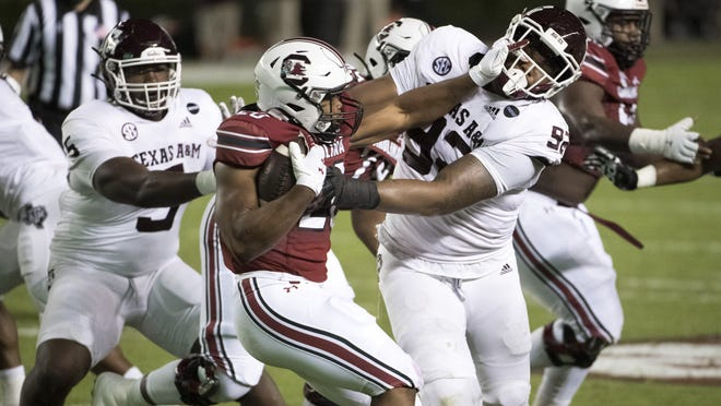 South Carolina running back Kevin Harris stiff-arms Texas A&M defensive lineman Jayden Peevy during Texas A&M's 48-3 win Saturday in Columbia, S.C. Harris, the SEC's second-leading rusher coming in, was limited to 39 yards on 13 carries.