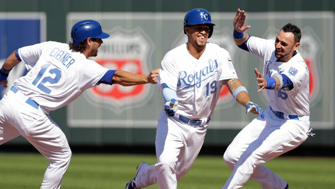 Cheslor Cuthbert, center, is chased down by Brett Eibner, left, and Paulo Orlando, right, as they celebrate his game-winning hit in the 13th inning.