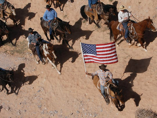 In this April 12, 2014, file photo, the Bundy family and their supporters fly the American flag as their cattle is released by the Bureau of Land Management back onto public land outside of Bunkerville, Nevada.