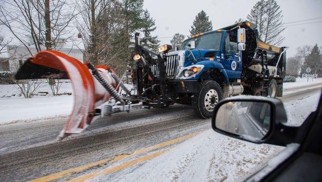 A town plow passes through Williston as snow falls on Monday, December 5, 2016.