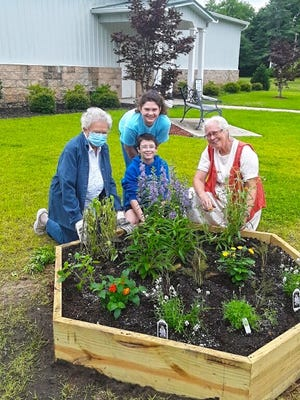 Myrtle Quattlebaum, Sophie Nelson, Rhys Nelson, and Lil  Stoltzfus show off the new raised pollinator planter at the corner of Main and Walker streets that the Blackville Garden Club installed for National Garden Week.