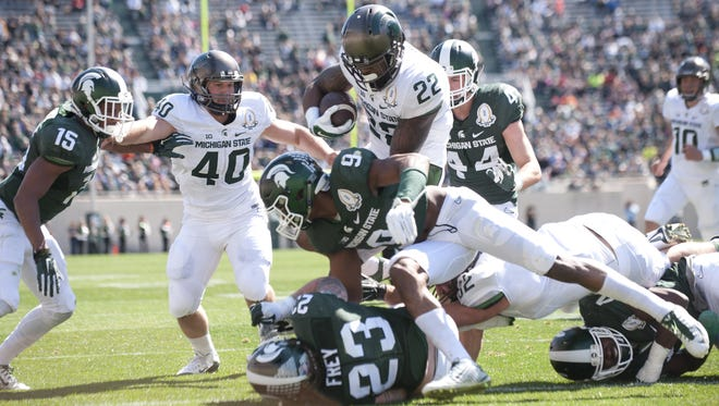 White team running back Delton Williams (22) scores a touchdown over Green team safety Montae Nicholson (9) and linebacker Chris Frey (23) during the Green and White Spring Game on Saturday, April 23, 2016 at Spartan Stadium.