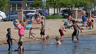 Children enjoy frolicking in Pewaukee Lake as parents sit on the beach and enjoy the sun.