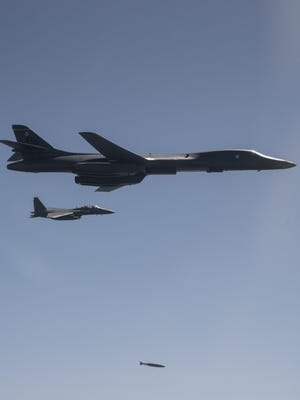 A U.S. Air Force B-1B Lancer, flanked by Republic of Korea Air Force F-15K Slam Eagles, drops a 2,000 pound live munition at Pilsung Training Range, South Korea on Sept. 18 as a part of a show of force mission in response to North Korean unsanctioned intercontinental ballistic missile tests. The most recent test took place last Friday and overflew the Japanese island of Hokkaido, resulting in increased tensions in both Japan and the Republic of Korea.