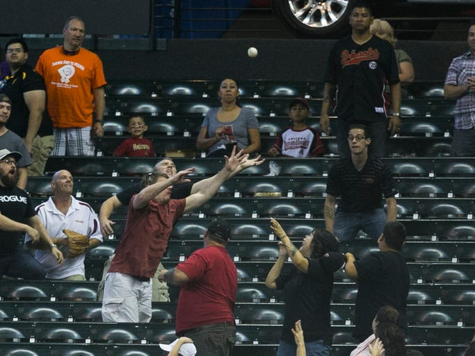 Fans reach to grab a home run hit by Padres' Yasmani Grandal in the fifth inning against the Diamondbacks at Chase Field in Phoenix on Sunday, Aug. 24, 2014.