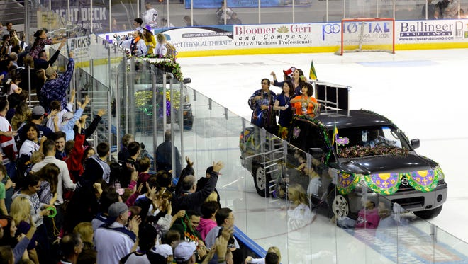 Fans shout for beads during the Mardi Gras Parade on Ice after the first period Sunday against the Macon Mayhem at the Pensacola Bay Center.