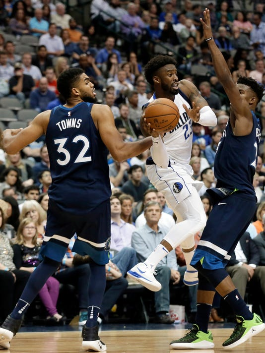 Minnesota Timberwolves center Karl-Anthony Towns (32) and guard Jimmy Butler, right, defend as Dallas Mavericks' Wesley Matthews (23) passes the ball out in the second half of an NBA basketball game, Friday, Nov. 17, 2017, in Dallas. (AP Photo/Tony Gutierrez)