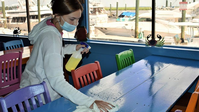 Taylor Killion disinfects a table at Fish Tales Restaurant as part of an overall plan to keep customers safe.